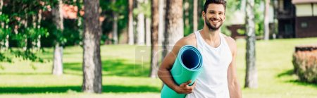 panoramic shot of happy athletic sportsman holding fitness mat in park