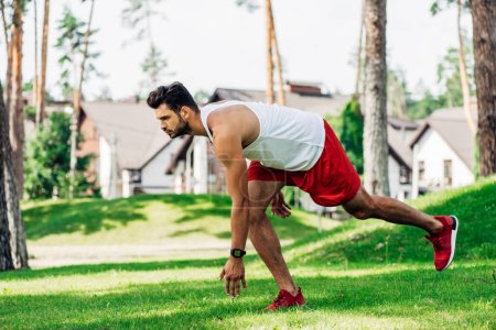 handsome bearded athletic sportsman training in park