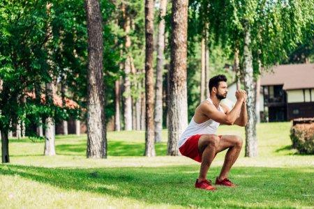 bearded athletic sportsman training in park on green lawn