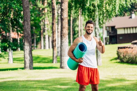 Photo for Happy athletic sportsman holding fitness mat and showing thumb up - Royalty Free Image