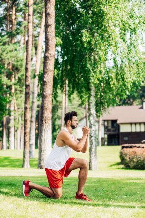 Photo for Profile of bearded man training on grass in park - Royalty Free Image