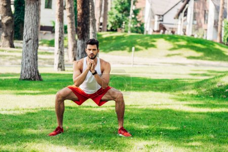 Photo for Athletic bearded man training on grass in park - Royalty Free Image