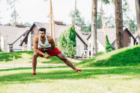 handsome man warming up while exercising on lawn