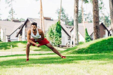 Photo pour Bel homme échauffement tout en exerçant sur la pelouse - image libre de droit