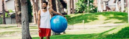 Photo pour Plan panoramique de l'homme heureux tenant ballon de fitness bleu dans le parc - image libre de droit
