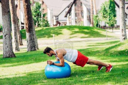 bearded man in sportswear exercising on blue fitness ball in park