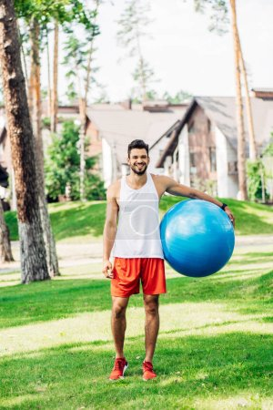 Photo for Happy sportsman standing on green grass and holding blue fitness ball - Royalty Free Image