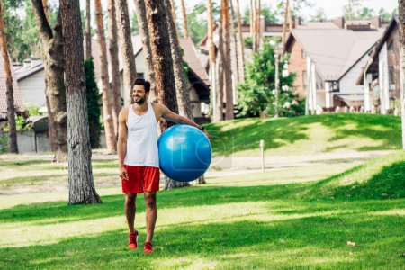 happy sportsman walking on green grass and holding  fitness ball