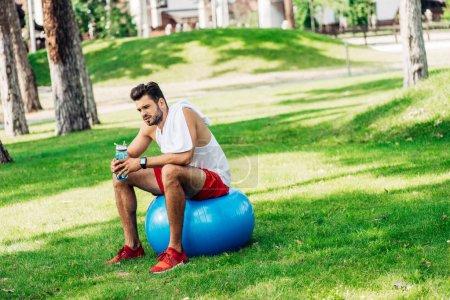Photo pour Sportif barbu tenant une bouteille de sport assis sur une balle de fitness - image libre de droit