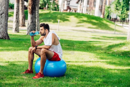 Photo for Bearded sportsman drinking water from sport bottle while sitting on fitness ball - Royalty Free Image