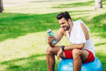 Photo for Happy bearded man looking at sport bottle while sitting on fitness ball - Royalty Free Image