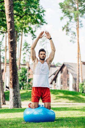 Photo for Handsome bearded man working out on fitness ball in park - Royalty Free Image