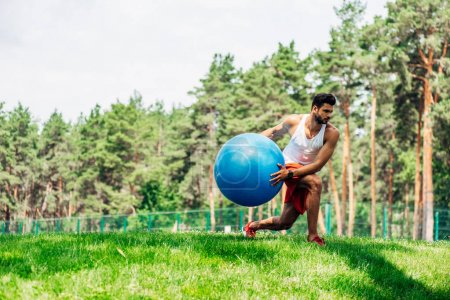 Photo for Handsome sportsman training with fitness ball in park - Royalty Free Image