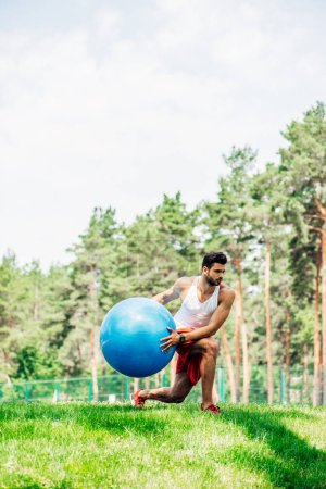 Photo for Handsome sportsman exercising with fitness ball in park - Royalty Free Image