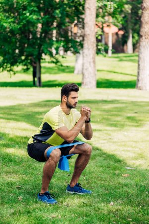 Photo for Handsome man exercising with suspension straps in park - Royalty Free Image