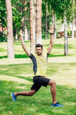handsome bearded sportsman exercising on green lawn