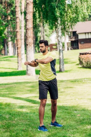 handsome young sportsman working out in park on grass