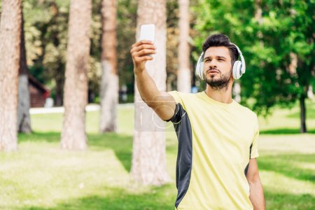 Brodatego człowieka robienia selfie, trzymając smartfon i słuchanie muzyki w słuchawkach