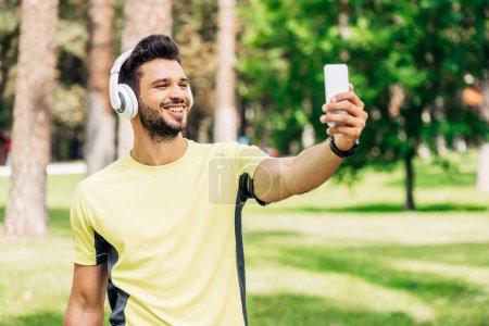 hombre barbudo feliz tomar selfie mientras sostiene el teléfono inteligente y escuchar música en los auriculares
