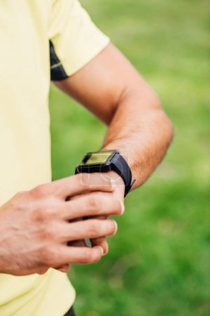 Photo for Cropped view of sportsman touching fitness tracker outside - Royalty Free Image