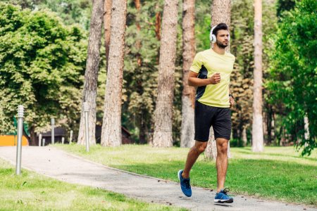 Photo for Handsome bearded man running while listening music in headphones in park - Royalty Free Image