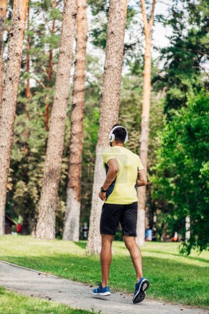 Photo for Back view of man running while listening music in headphones in park - Royalty Free Image
