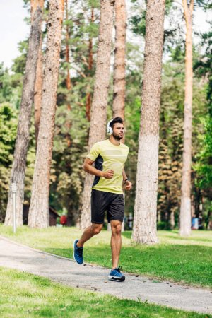 Photo for Sportsman jogging while listening music in headphones in park - Royalty Free Image