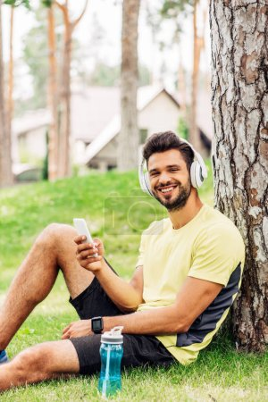 Photo for Happy man in headphones sitting near tree trunk and holding smartphone - Royalty Free Image