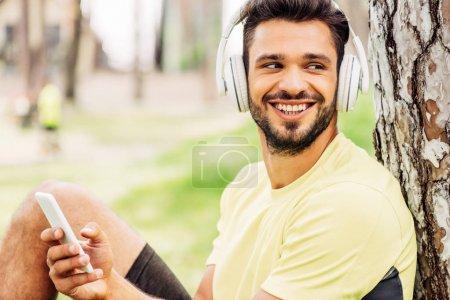 Photo pour Homme barbu joyeux écouter de la musique et en utilisant smartphone dans le parc - image libre de droit
