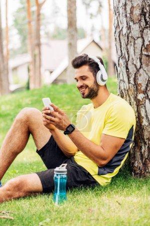 Photo pour Sportif heureux dans les écouteurs en utilisant un smartphone près du tronc d'arbre et écouter de la musique - image libre de droit