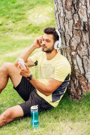 handsome sportsman in headphones using smartphone near tree trunk and listening music