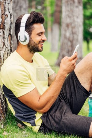 Photo for Happy man listening music and using smartphone in park - Royalty Free Image