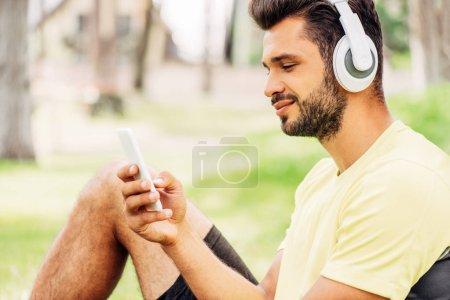 happy bearded man listening music and using smartphone