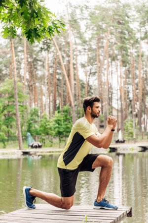 handsome and athletic man in sportswear exercising near lake in forest