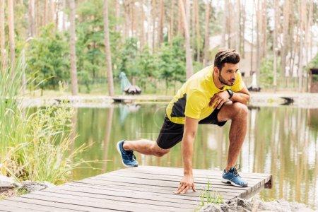 Photo pour Bel homme barbu en tenue de sport faisant de l'exercice près du lac en forêt - image libre de droit