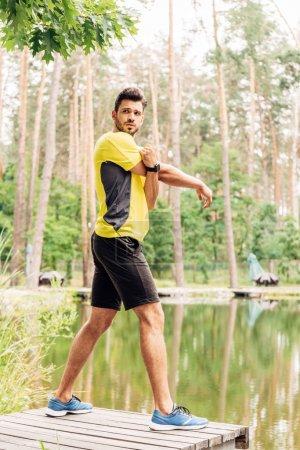 Photo pour Bel homme barbu faisant de l'exercice près du lac dans la forêt - image libre de droit