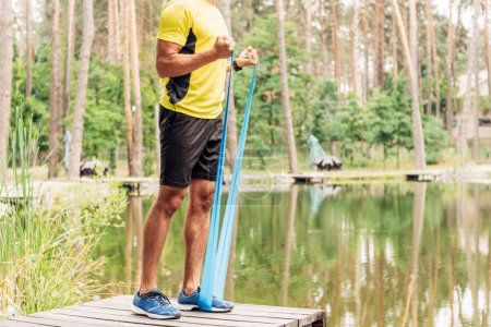 Photo for Cropped view of sportsman exercising with suspension straps near lake - Royalty Free Image