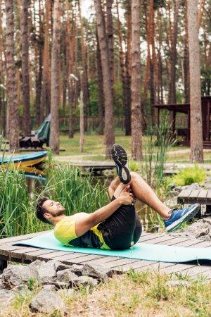 Photo pour Sportif travaillant sur tapis de fitness dans la forêt près des arbres et des pierres - image libre de droit