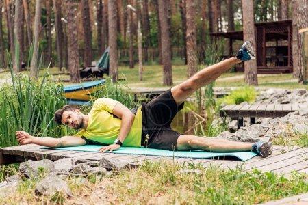 Photo pour Homme barbu dans l'entraînement de vêtements de sport sur tapis de fitness près des pierres et des arbres - image libre de droit