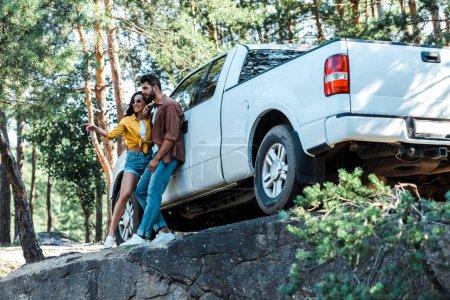 Photo pour Vue basse d'angle de la femme heureuse restant près de l'homme et de la voiture barbus dans les bois - image libre de droit