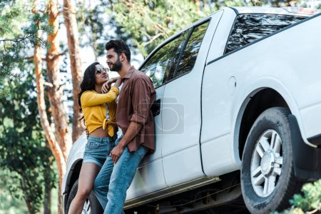 Photo for Low angle view of attractive girl in sunglasses standing with bearded man near car - Royalty Free Image