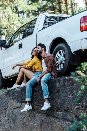 Photo for Happy bearded man and attractive girl sitting near car in woods - Royalty Free Image