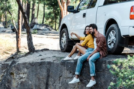 Photo for Happy bearded man and attractive girl sitting near car and trees - Royalty Free Image