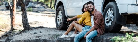 Photo for Panoramic shot of happy bearded man and attractive girl sitting near car and trees - Royalty Free Image