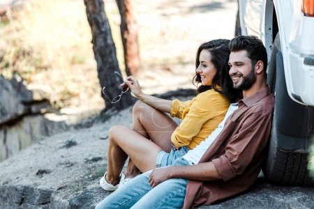 Photo for Cheerful bearded man and attractive girl sitting near car and trees - Royalty Free Image
