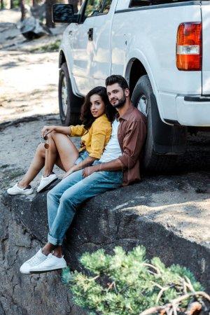 Photo pour Homme beau et barbu s'asseyant près de la voiture avec la femme attirante - image libre de droit