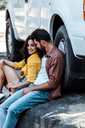 Photo pour Homme beau et barbu avec les yeux fermés assis près de la voiture avec une femme attrayante - image libre de droit