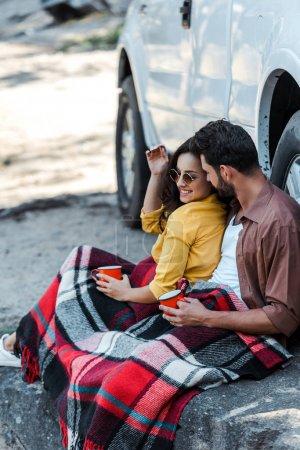 Photo pour Homme barbu et fille heureuse dans des tasses de fixation de lunettes de soleil près de la voiture - image libre de droit