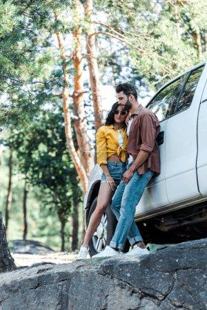 Photo pour Homme barbu heureux et fille gaie dans des lunettes de soleil restant près de la voiture dans les bois - image libre de droit