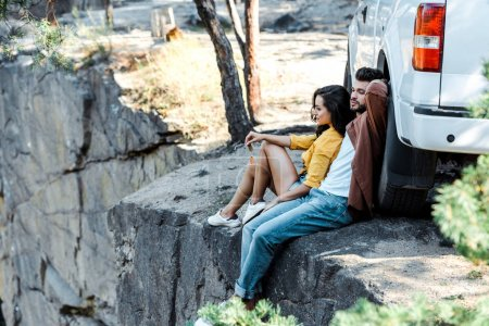 Photo for Selective focus of handsome man and attractive girl sitting near car - Royalty Free Image